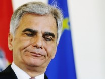 Austria's Chancellor Faymann listens during a news conference in Vienna