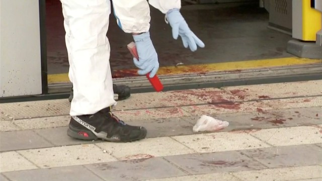 An police investigator looks at bloodstained footprints leading out of a train and on a platform  following a knife attack in Grafing train station, south east of Munich, Germany