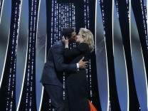 Master of Ceremony actor Laurent Lafitte kisses actress Catherine Deneuve on stage during the opening ceremony of the 69th Cannes Film Festival in Cannes