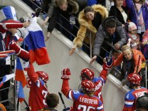 Russian players are congratulated by fans as they leave the ice after they defeated Germany in their women's ice hockey game at the 2014 Sochi Winter Olympics