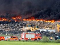 Emergency workers stand next to a fire at a tire dump near a residential development in Sesena, south of Madrid