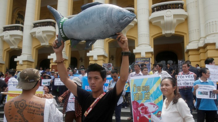 Demonstrators, holding signs of environmental-friendly messages, say they are demanding cleaner waters in the central regions after mass fish deaths in recent weeks, in Hanoi, Vietnam