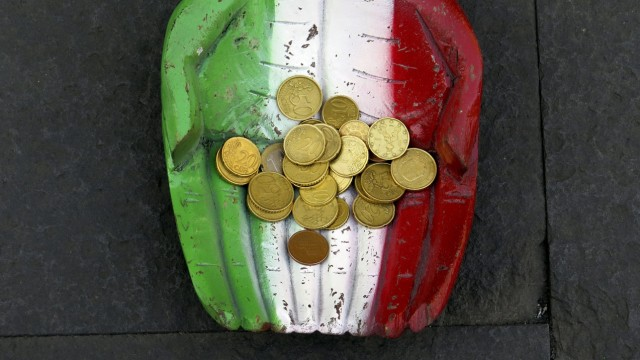 File photo of Euro coins seen on the figure of a pair of hands, which are painted in Italy's colour national colours, on the ground in downtown Rome