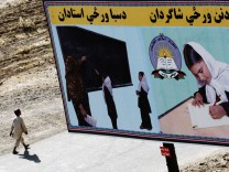 An Afghan boy walks past a billboard encouraging girls to go to school in Kandahar City