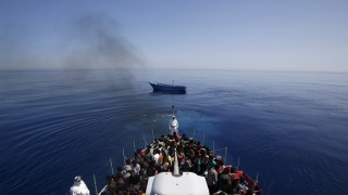 A group of 300 sub-Saharan Africans sit in board at Italian Finance Police vessel Di Bartolo as their boat  is left to adrift off the coast of Sicily