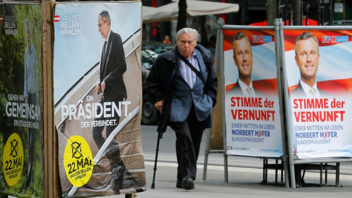 A man passes by presidential election campaign posters of Van der Bellen, supported by the Greens party, and Hofer of the FPOe in Vienna