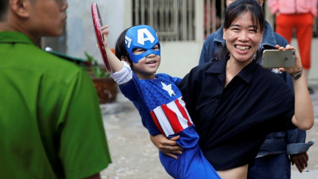A kid dressed as Captain America waves at U.S. President Barack Obama's motorcade during Obama's arrival at Ho Chi Minh City