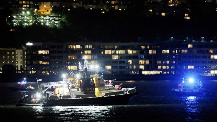 An FDNY fire department boat searches the Hudson River for the wreckage of a vintage P-47 Thunderbolt airplane that crashed in the river in New York City