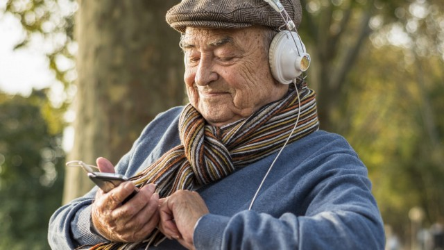 Senior man on park bench with cell phone and headphones model released Symbolfoto PUBLICATIONxINxGER