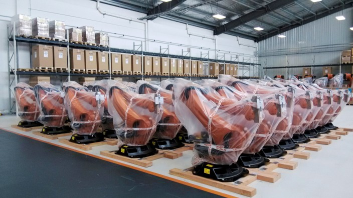 Robots covered in plastic sheets are seen at a plant of Kuka Robotics in Shanghai