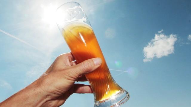 Glas mit Weizenbier an einem heißen Sommertag mit blauem Himmel in einem Biergarten am Titisee Bade