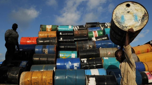 Men stack oil barrels at a depot in Santo Domingo