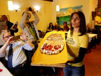 Virginia Raggi, the anti-establishment 5-Star Movement's candidate for Rome mayor, holds a pizza during a fund-raising event in Rome