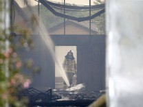 A firefighter extinguishes fire at fair halls used as refugee camps in Duesseldof