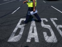 A truck driver walks along a BASF sign on the road near the warehouse of German chemical company BASF in Ludwigshafen