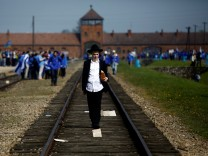 A man walks on the railway tracks in the former Nazi death camp of Auschwitz-Birkenau (Auschwitz II) as thousands of people, mostly youth from all over the world gathered for the annual 'March of the Living' to commemorate the Holocaust in Brzezinka