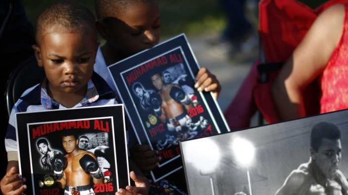 Infant holds an image of Muhammad Ali during the funeral procession for the three-time heavyweight boxing champion in Louisville