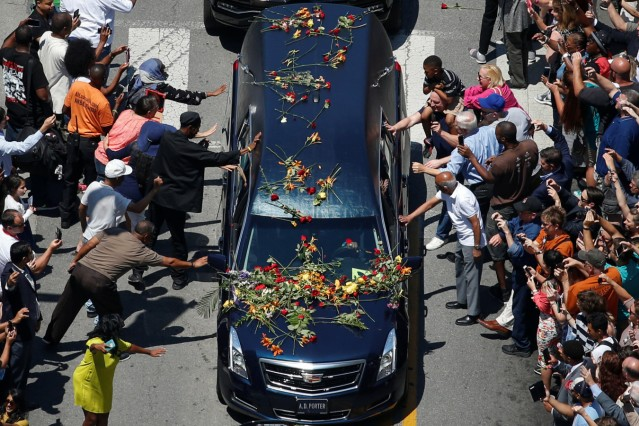 Well-wishers touch the hearse carrying the body of the late boxing champion Muhammad Ali during his funeral procession through Louisville, Kentucky