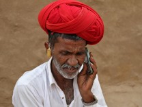 A man talks on his mobile phone in the village of Devmali in the desert state of Rajasthan
