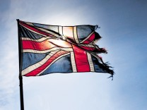 Torn Union Jack flag flying