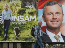 A man passes presidential election campaign posters of Van der Bellen and Hofer in Vienna