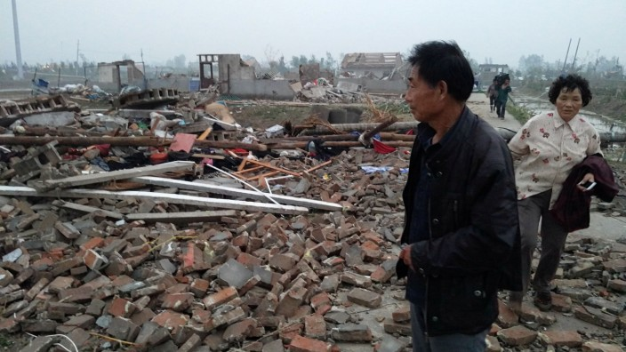 A man stands on debris of houses after a tornado hits Funing county, Yancheng