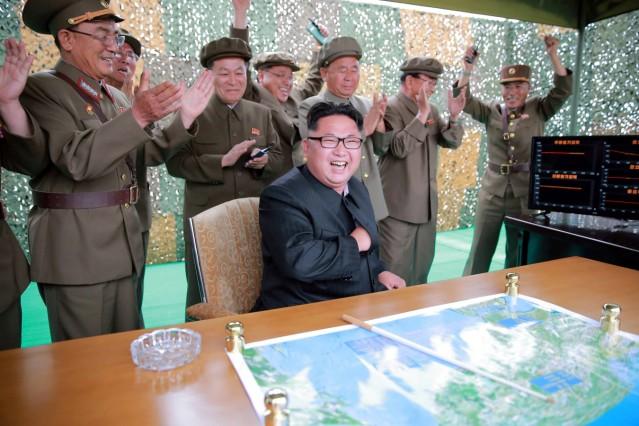 North Korean leader Kim Jong Un reacts during a test launch of ground-to-ground medium long-range ballistic rocket Hwasong-10