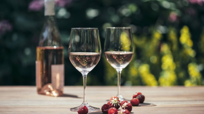 Two glasses of rose wine wine bottle strawberries and raspberries on wooden table PUBLICATIONxINxG