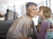 Grandmother getting a kiss from grandchild who received a gift model released Symbolfoto property re
