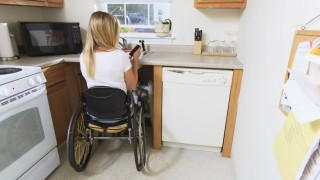 Woman with spinal cord injury in kitchen MODEL RELEASED Woman with spinal cord injury in her access