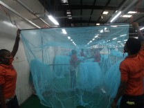 Workers look for abnormal holes in mosquito netting at the A to Z Textile Mills factory producing insecticide-treated bednets in Arusha, Tanzania