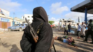 A Somali government soldier views the dead bodies of suspected al-Shabaab militant fighters killed in a suicide bomb attack outside Nasahablood hotel in Somalia's capital Mogadishu