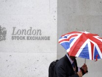 A worker shelters from the rain as he passes the London Stock Exchange in the City of London