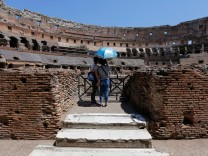 Tourists use an umbrella to protect themselves from the sun as they visit the Colosseum in Rome