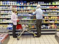 Supermarkt Lebensmittel älteres Seniorenpaar beim einkaufen Kühlregal mit Milch Molkerei Produkte