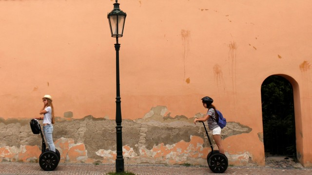 Tourists ride on Segways through a street in central Prague