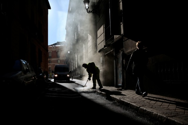 A worker fixes a street pavement in central Madrid