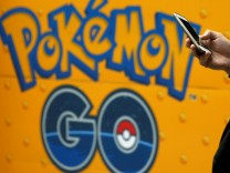 A man uses a mobile phone in front of an advertisement board bearing the image of Pokemon Go at an electronic shop in Tokyo