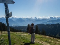 Eine Frau steht mit Ihrem Rucksack an einer Wegkreuzung mit Wegweisern und schaut in die Ferne Bald