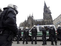 German riot police stand in front of the Cologne Cathedral during a protest of supporters for Turkish President Erdogan in Cologne