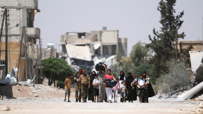 Syria Democratic Forces (SDF) fighters walk with people that fled their homes due to clashes between Islamic State fighters and Syria Democratic Forces (SDF) towards safer parts of Manbij, in Aleppo Governorate