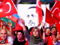 Supporters of Turkish President Erdogan wave national flags as they listen to him through a giant screen in Istanbul's Taksim Square