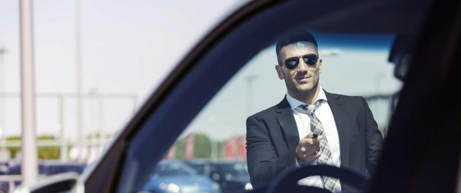 Businessman at car park opening car model released Symbolfoto PUBLICATIONxINxGERxSUIxAUTxHUNxONLY MA