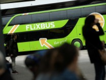 Passengers walk near Flixbus bus at main bus station in Berlin