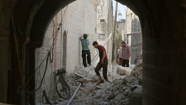 Residents inspect their damaged homes after an airstrike on the rebel-held Old Aleppo