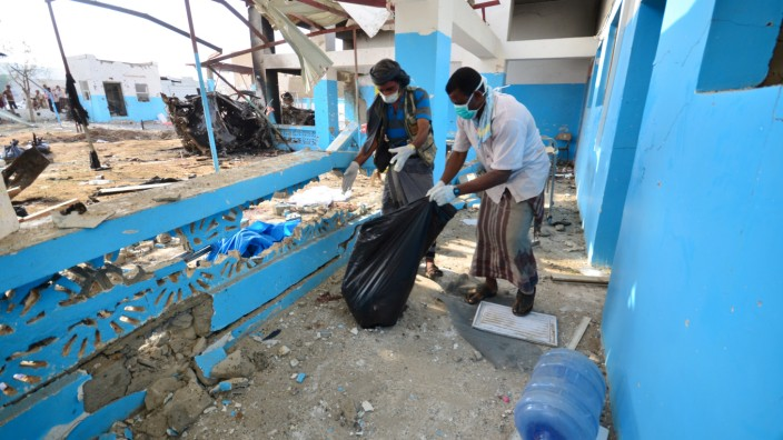 Workers collect human remains at the yard of a hospital operated by Medecins Sans Frontieres after it was hit by a Saudi-led coalition air strike in the Abs district of Hajja province, Yemen