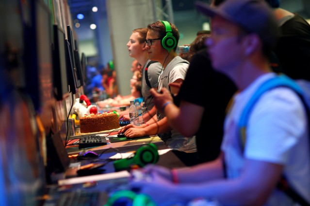 Visitors play the video game 'Superverse' during the Gamescom fair in Cologne