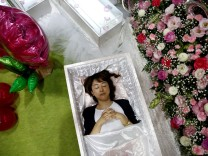 A staff lies in a casket next an altar decorated with flowers and balloons as she demonstrates Okuribito funeral's funeral service at the Life Ending Industry Expo in Tokyo