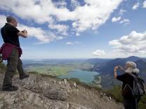 Blick vom Gipel des Herzogstands auf den Kochelsee, im Vordergrund fotografierende Bergwanderer