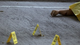 Evidence markers are seen next to a slain body at a crime scene in Tegucigalpa